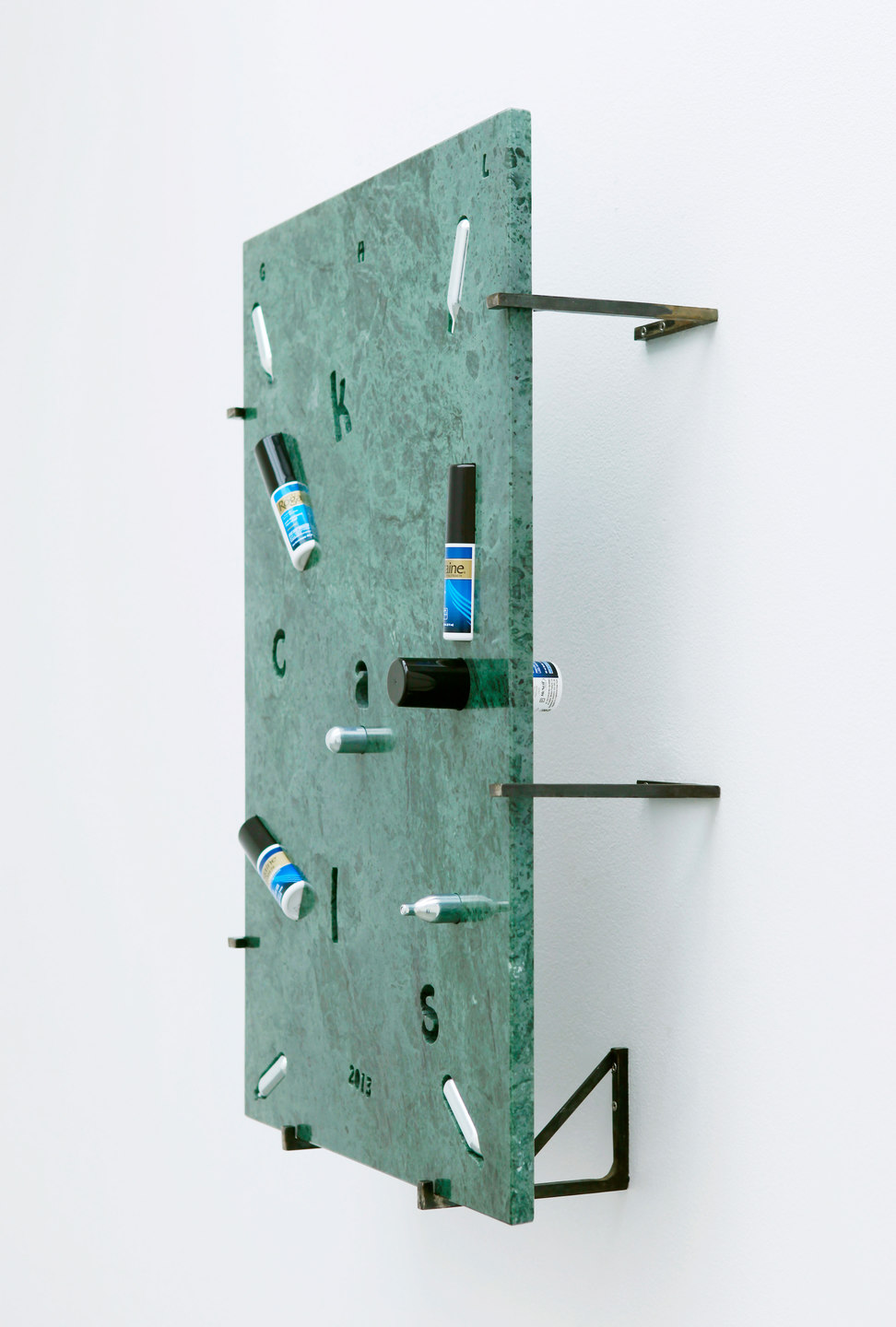 George Henry Longly, 2013: Year of the Snake, 2013, Verde Guatamala marble, whipping cream, chargers (nitrous oxide / laughing gas), Regaine (UK), Rogaine (US), Manifique (gay magazine), steel stand off fixings, 57 x 82 x 18 cm, Cell Project Space