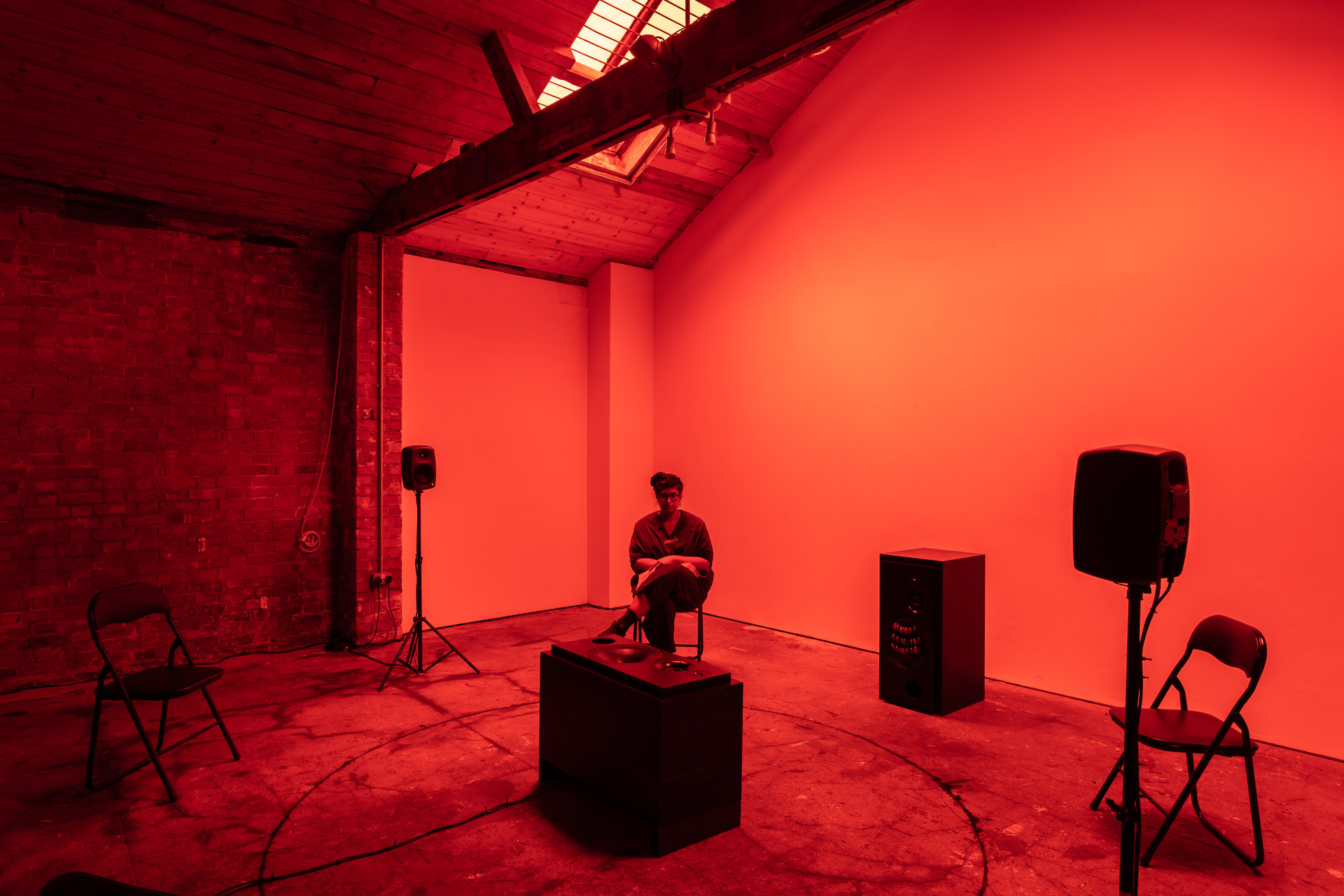 Shenece Oretha, Called To Respond, 2020 Installation View active speakers, chicken bones, cymbals, rehearsal chairs, lighting gel
