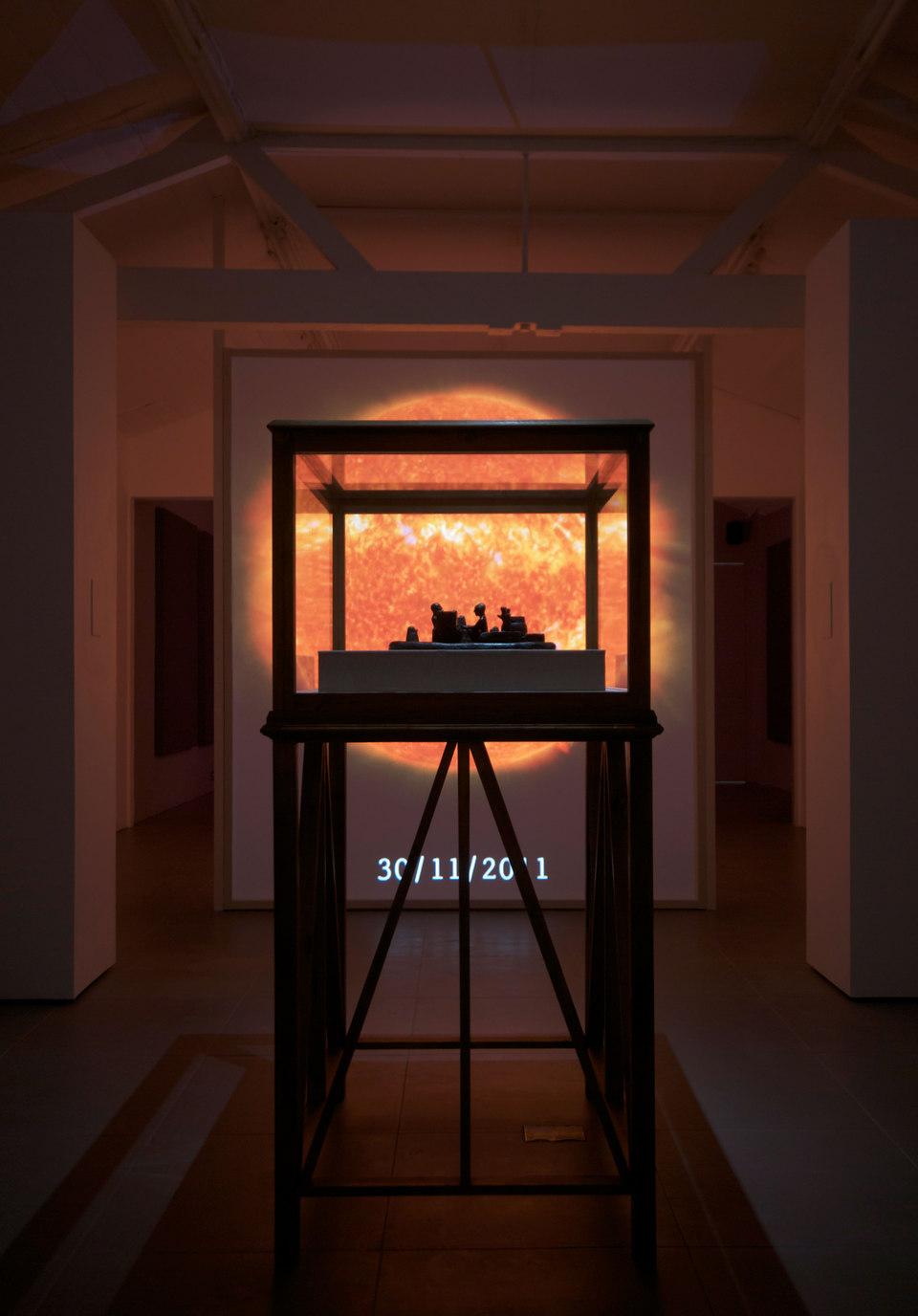 SO-LA, 2012, digital video, duration variable, 'Reconstruction of a 12th century BC Elamite antiquity, Sit Shamsi', 2012, bronze,(w. 53 cm x h. 12 cm x d. 35 cm) with 'Vitrine', 2012, timber, acrylic, linen, (w. 100 cm x h. 165 cm x d. 79 cm)